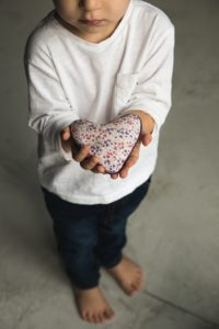 Young boy holding toy shaped like a heart - family philanthropy can begin at any age