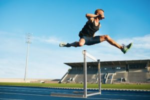 Professional sprinter jumping over a hurdle, representing clearing hurdles to wealth and success