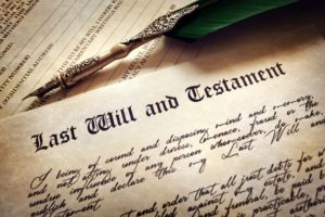 """Close up image of a pen and document reading """"last will and testament"""" as a symbol for preparing wills and trusts"""