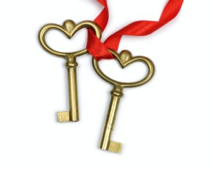 Two simple gold keys with a red ribbon symbolizing the a family stewards role to support the family through focus and dedication