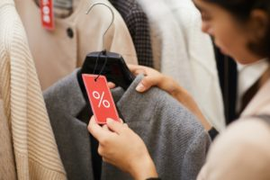 Young woman choosing clothes on sale - symbolizing savvy spending