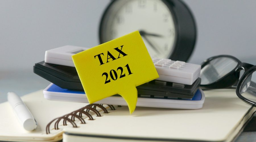 Clock, calculator, notebook, and a speech bubble with tax 2021 written inside - related to federal income tax filing in 2021