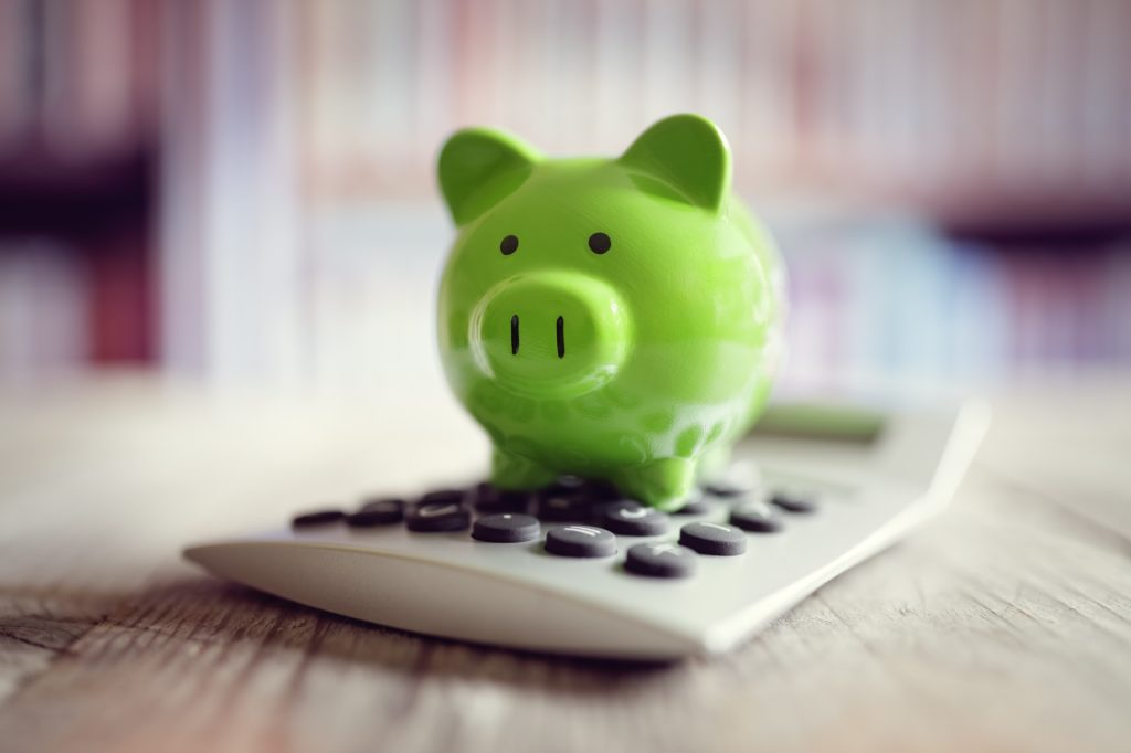 Concept: thinking about strategic charitable giving vs small cash donations description: piggy bank with calculator